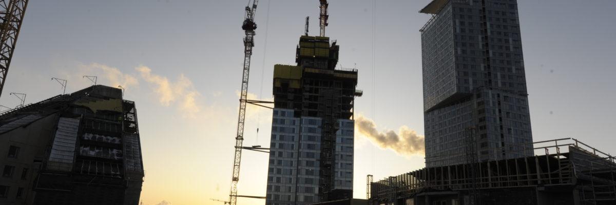 Kuvassa rakennettavia taloja ja nosturi siluettina auringonlaskua vasten